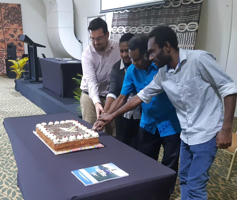 Hon. Ham Lini with national stakeholder representatives during the cake cutting to launch the Report